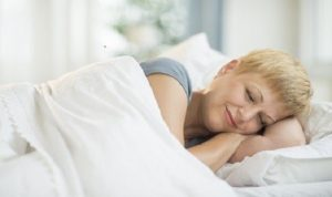 Mature woman smiling while sleeping in bed at home